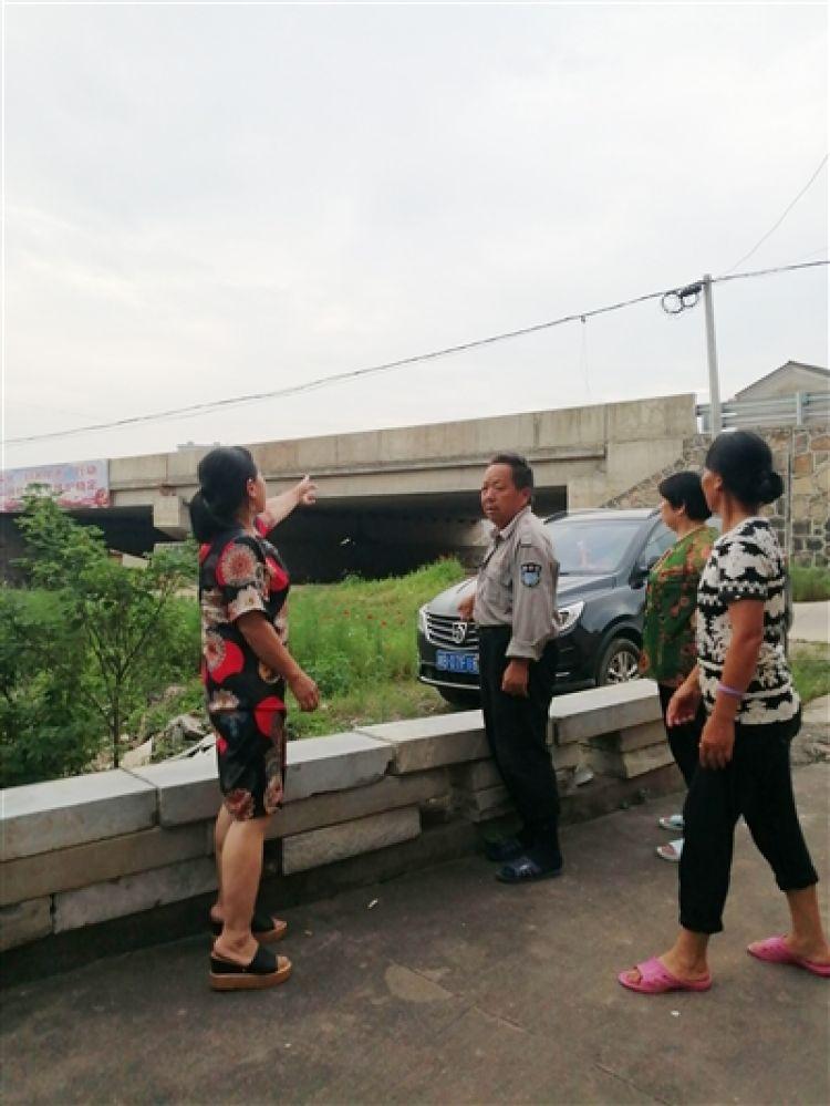 上洲社区居民彭云兰(左一)哭着说,她现在还能回忆起当时张清月捂着胸口,从桥上涉水而过的样子。/记者 陈驰 摄
