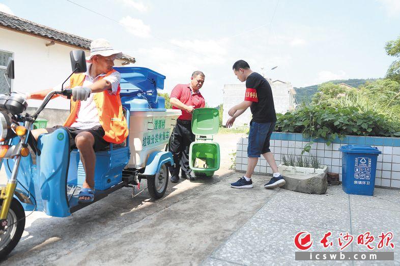 """在澄潭村,参加主题党日活动的""""党员督导员""""帮助保洁员把可回收垃圾放上车。                     颜开云 摄"""